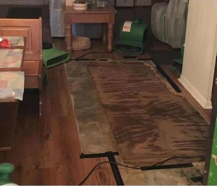 Air movers drying wooden floor