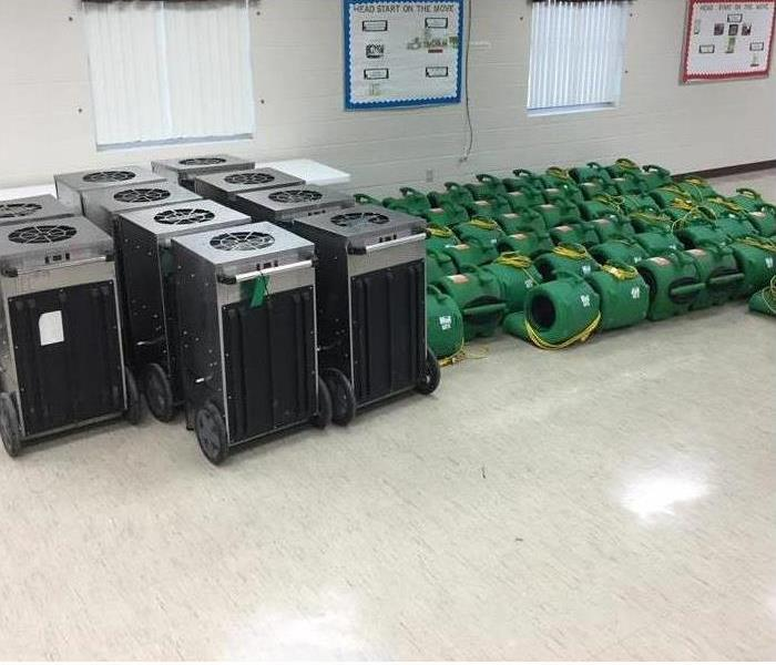 Air movers, dehumidifiers and other equipment in a room ready to be used