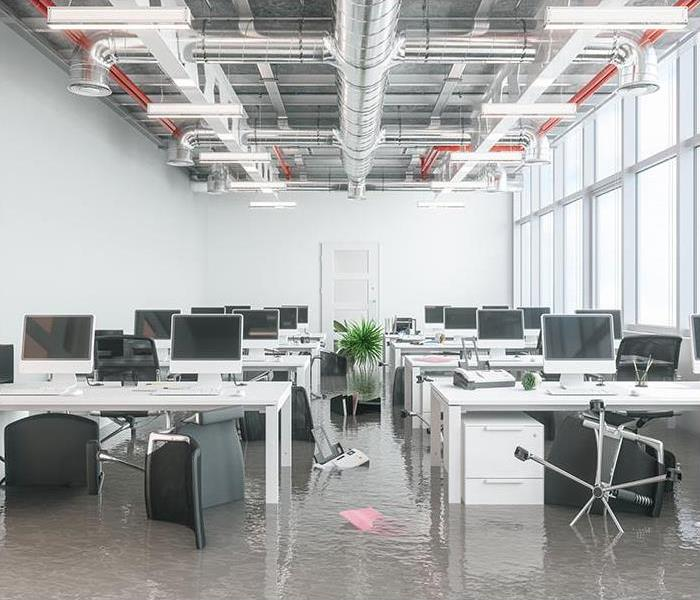 Office space with rows of desks and the floor covered in water