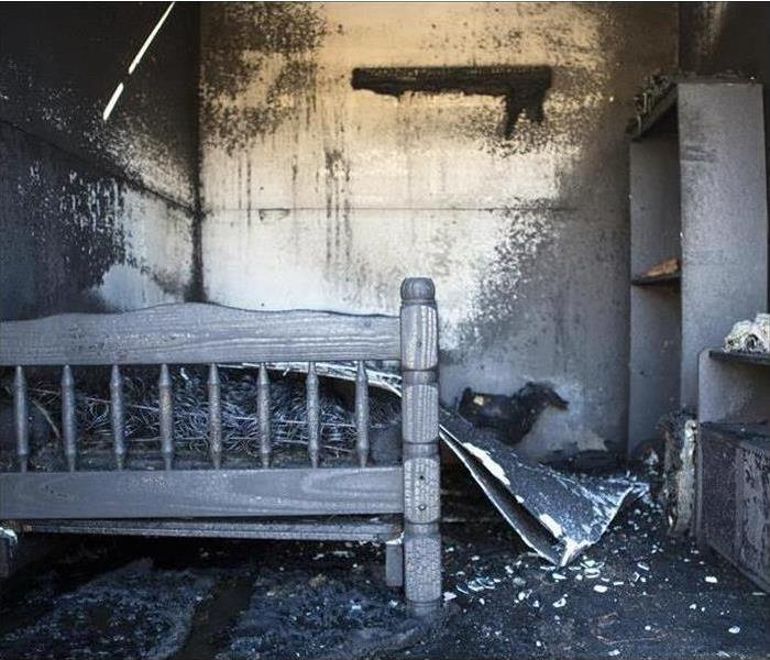 Soot and fire damage all over the walls, bed, and shelving in a bedroom.